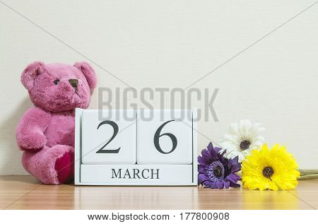 Closeup surface white wooden calendar with black 26 march word on brown wood desk and cream color wallpaper in room textured background with copy space selective focus at the calendar
