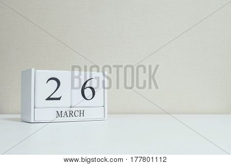 Closeup white wooden calendar with black 26 march word on blurred white wood desk and cream color wallpaper in room textured background with copy space selective focus at the calendar