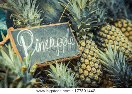 Pineapple background. Exotic pineapples background with chalk word Pineapple.