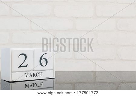 Closeup white wooden calendar with black 26 march word on black glass table and white brick wall textured background with copy space selective focus at the calendar