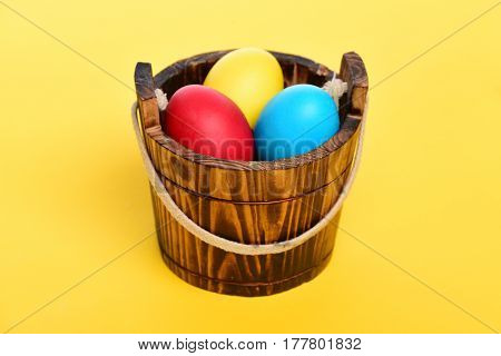 Painted Easter Colorful Eggs In Wooden Bucket On Yellow Background