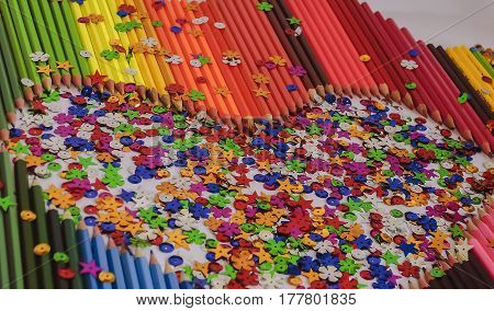 Colour pencils laid out on a white background in the form of hearts and scattered multi-colored candy.