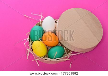 Painted Easter Colorful Eggs In Wooden Box On Pink Background
