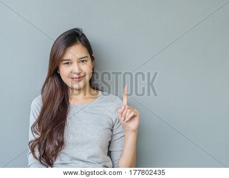 Closeup asian woman holds up one finger with smile face on blurred cement wall textured background with copy space