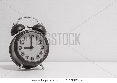 Closeup alarm clock for decorate in 9 o'clock on white wood desk and cream wallpaper textured background in black and white tone with copy space