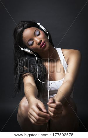 Young happy mixed race woman with beautiful makeup listening to music on earphones over black background