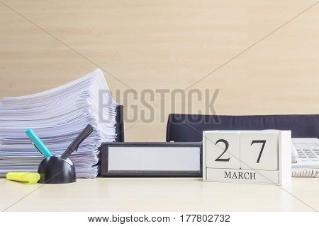 Closeup white wooden calendar with black 27 march word on blurred brown wood desk and wood wall textured background in office room view with copy space selective focus at the calendar