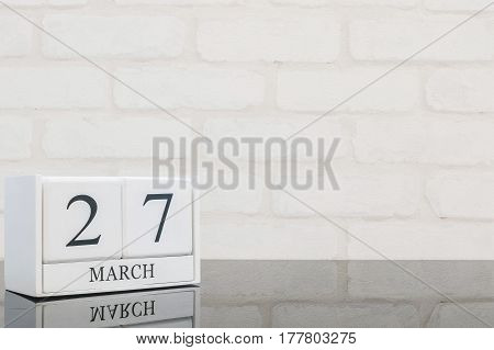 Closeup white wooden calendar with black 27 march word on black glass table and white brick wall textured background with copy space selective focus at the calendar