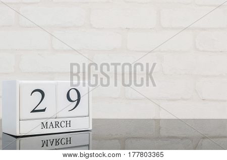 Closeup white wooden calendar with black 29 march word on black glass table and white brick wall textured background with copy space selective focus at the calendar
