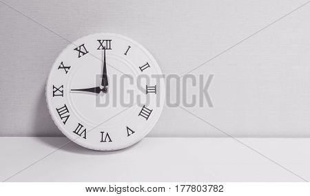 Closeup white clock for decorate in 9 o'clock on white wood desk and wallpaper textured background in black and white tone with copy space