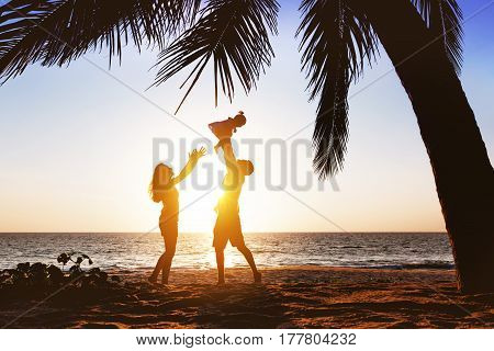 Happy family with little daughter having fun under palm tree on sunset beach background. Father tossing daughter