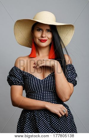 Woman in dress and hat on blank gray background