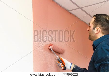 Rasit Hand Wall Paint Using A Paint Roller While Working Indoors