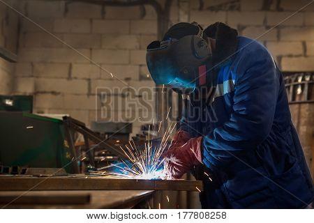 Industrial steel welder is working in the workshop