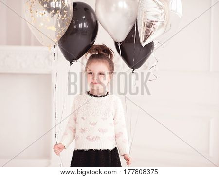 Smiling kid girl 5-6 year old holding helium balloons in room. Birthday party.