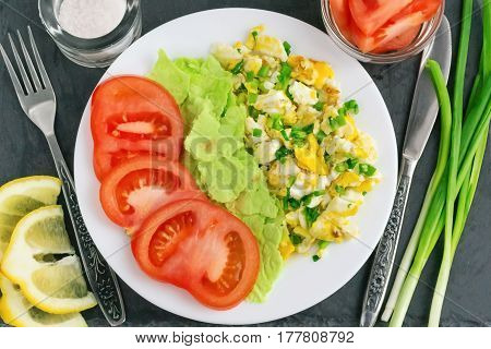 lemon slice, scrambled eggs, pita bread, tomatoes and onions for breakfast on a black background