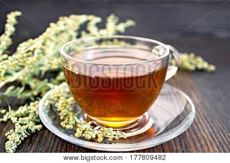 Herbal tea from wormwood in a glass cup on a saucer, gray sagebrush sprig on the background of dark wood planks