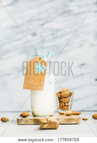 Fresh vegan dairy-free almond milk in glass bottle with craft paper label with copy space, grey marble background, selective focus. Vegan, vegetarian, raw, healthy, clean eating, detox food concept