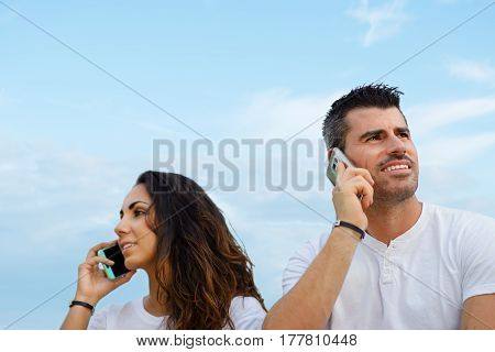 Man And Woman On Talking On Cellphones Against Sky Background