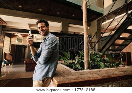 Portrait of handsome young man standing in modern office with mobile phone looking at camera and smiling. Business man taking break from work.
