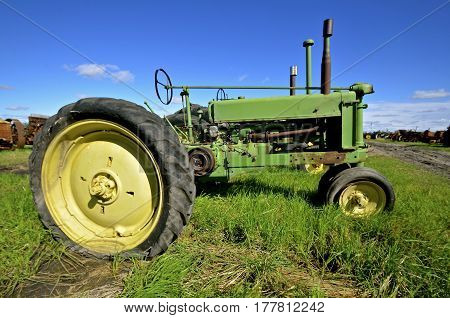 BARNESVILLE, MINNESOTA- September 26, 2016; An old green tractor left in the long grass is a producst of John Deere Co, an American corporation that manufactures agricultural, construction, forestry machinery, diesel engines, and drive trains