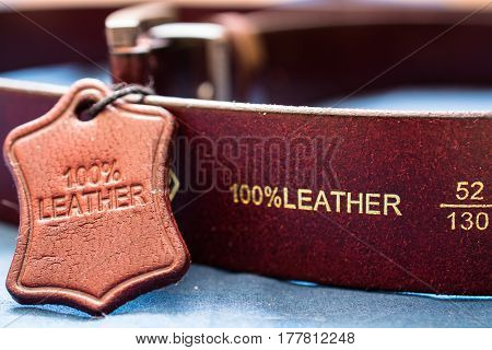 Part of red leather belt. Natural material label with caption.