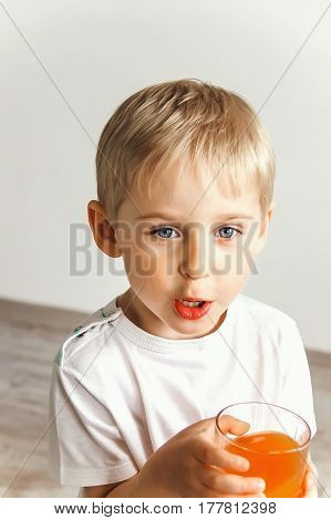 Cheerful Laughing Boy With Juice In The Glass,