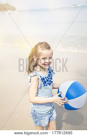 little girl with water ball at the beach