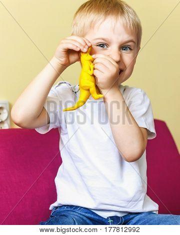 Happy Baby Boy Playing A Toy Dinosaur