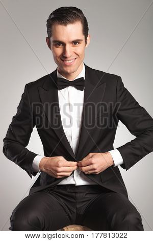 young elegant man unbuttoning his tuxedo while sitting on a wooden box in studio