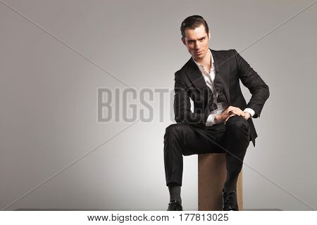 serious and elegant man sitting on wooden box with undone bowtie, on grey studio background
