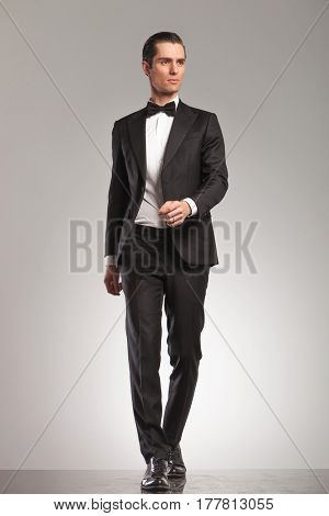 walking elegant man in tuxedo is looking up to side on grey studio background
