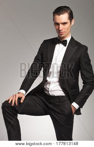 elegant man in tuxedo with one hand on knee and one in his pocket posing on grey background