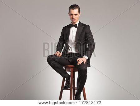 sexy elegant man in tuxedo and bowtie sitting on a stool on grey studio background