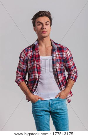 arrogant young casual man standing with hands in pockets in studio