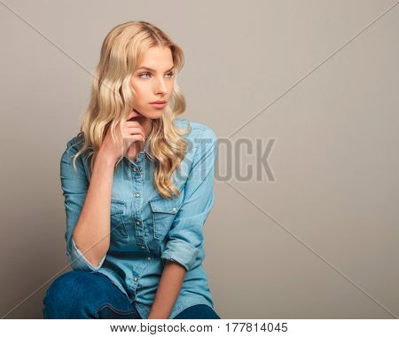 side view of a young casual woman sitting and looking away from the camera in studio