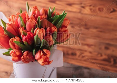 closeup picture of a tulips bouquet on wooden background