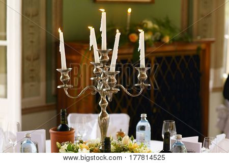 White candles burn standing in the old steel candleholder on a dinner table