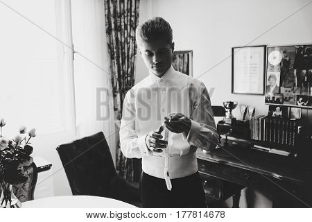 Handsome Man Looks Thoughtful Holding A White Tie In His Arms