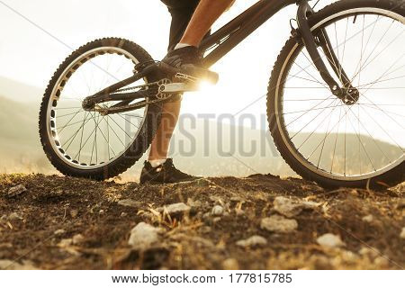 Horizontal outdoors shot of legs of sportsman on a trial bicycle treadle. Horizontal outdoors shot.