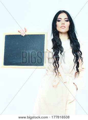 pretty cute sexy girl or beautiful woman with fashion makeup on serious face and curly long hair posing in beige velour bathrobe and holding board isolated on white background