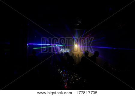 Silhouettes Of People And Musicians In Big Concert Stage. Bright Beautiful Rays Of Light A