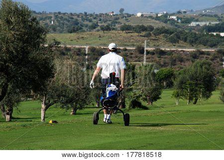 CALETA DE VELEZ, SPAIN - OCTOBER 27, 2008 - Golfer walking along with his buggy at Los Llanos de Baviera Golf Caleta de Velez Malaga Province Andalusia Spain Western Europe, October 27, 2008.