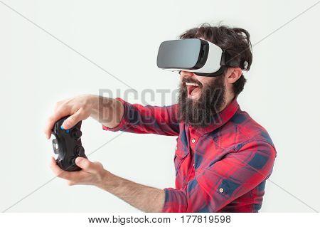 Playful man with gamepad and virtual reality goggles. Horizontal studio shot.