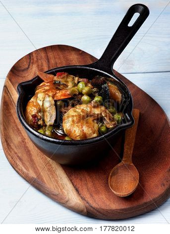 Delicious Seafood Curry with Prawns White Fish Mussels and Vegetables in Black Iron Cast Pot with Wooden Spoon closeup on Serving Board