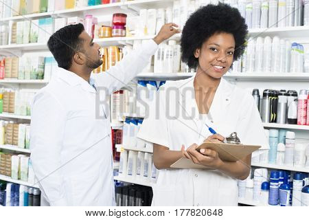 Pharmacist Writing On Clipboard While Colleague Arranging Produc