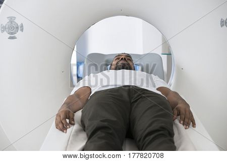 Male Patient Undergoing CT Scan In Examination Room