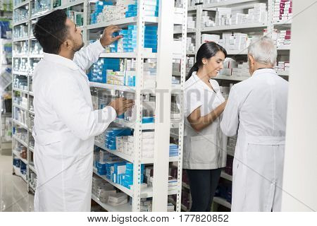 Chemist Arranging Stock While Colleagues Standing In Pharmacy