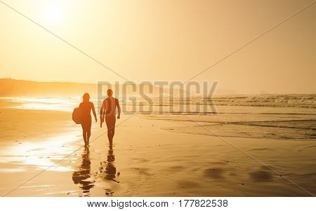 Couple Of Surfers On A Golden Sunset At The Beach