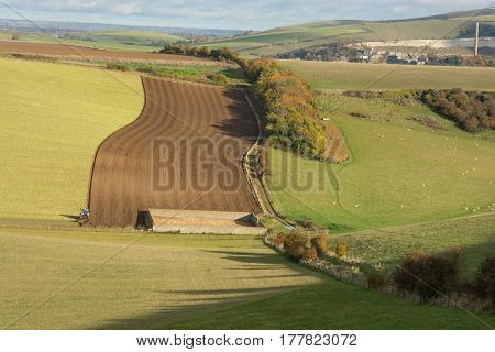Fields on the South Downs near Shoreham in West Sussex England. With tractor ploughing field.